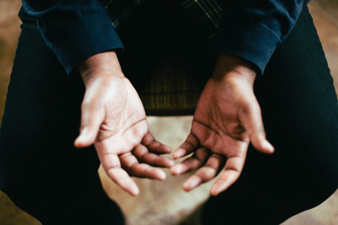 A man sits, holding his hands palms up in front of him